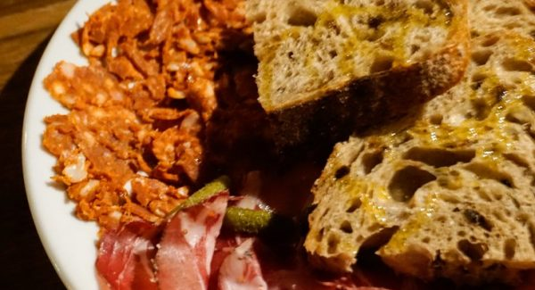 A big plate of Wage beef and British chorizo with servings of bread and pickles can experienced in restaurants in Leeds City Centre