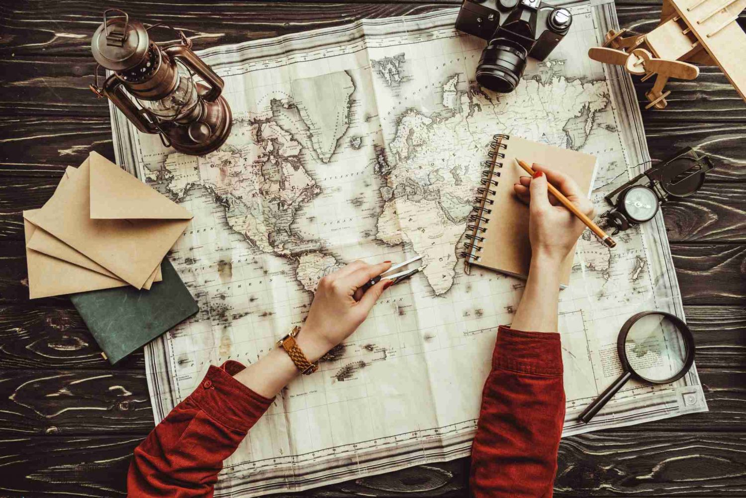 Birds' eye view of a woman in a red sweater recording her travel memories with a journal, map and postcards