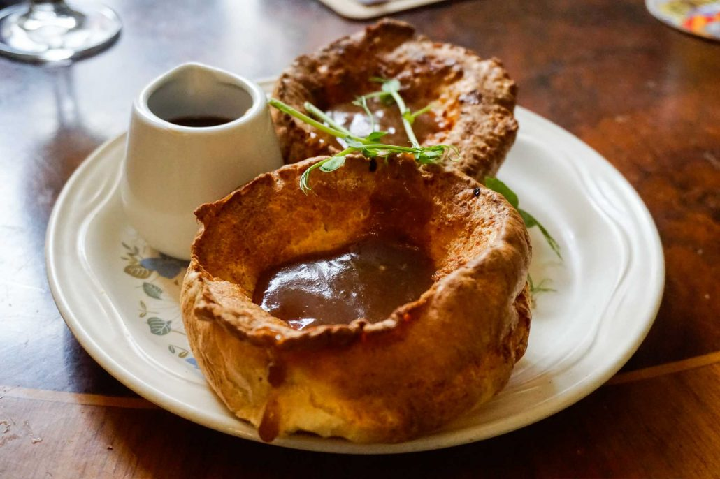 Discover a delicious close up of a big Yorkshire pudding filled with gravy and more to be poured into it in the best eateries and restaurants in Leeds City Centre