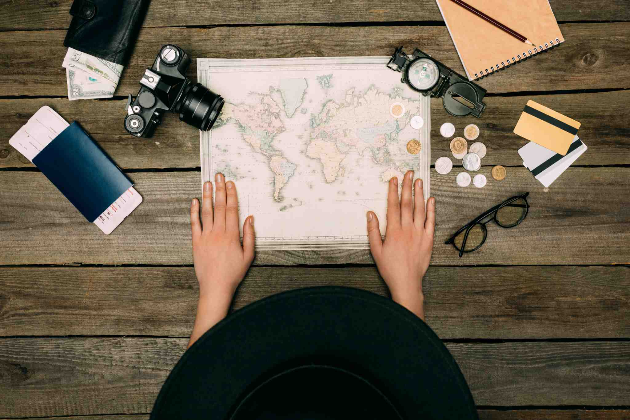 A bird's eye view of a woman looking at a map, a camera and some leftover currency
