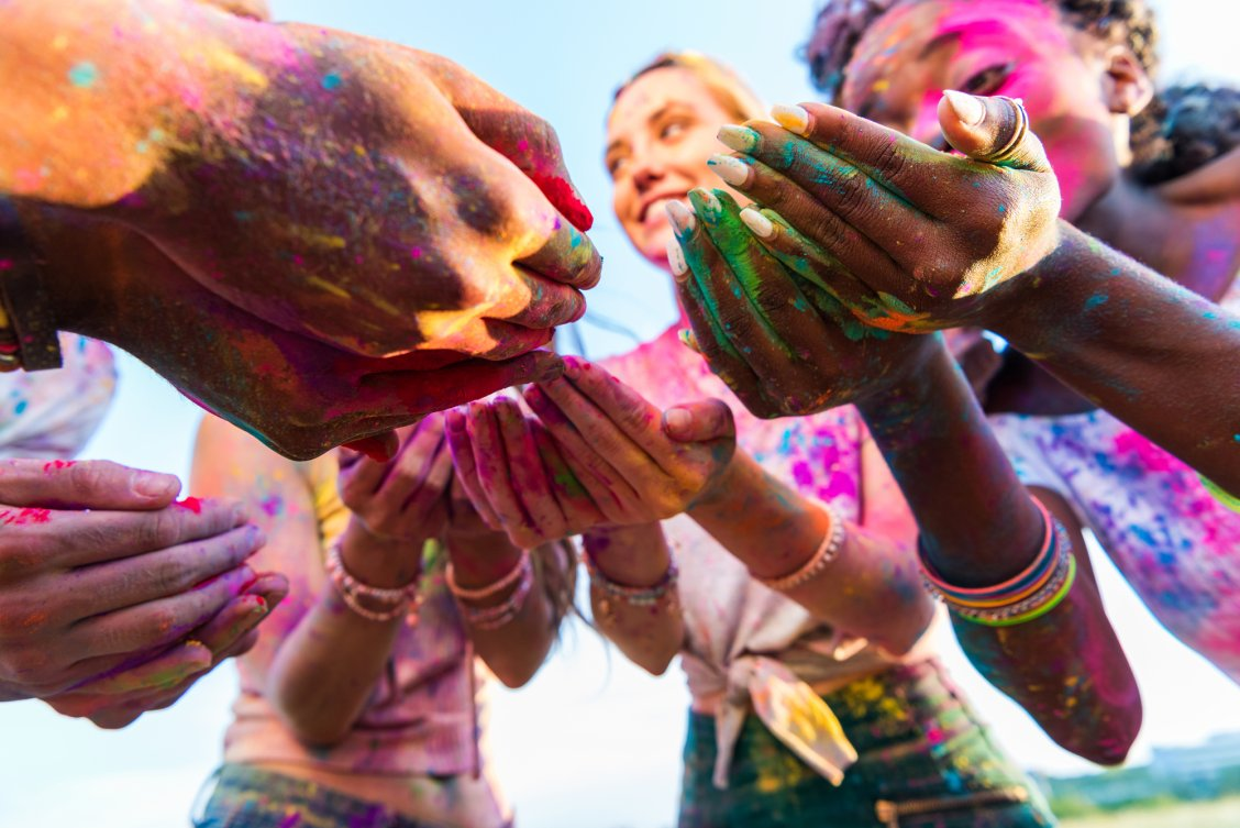Group of women in India covered in colours celebrating Holi