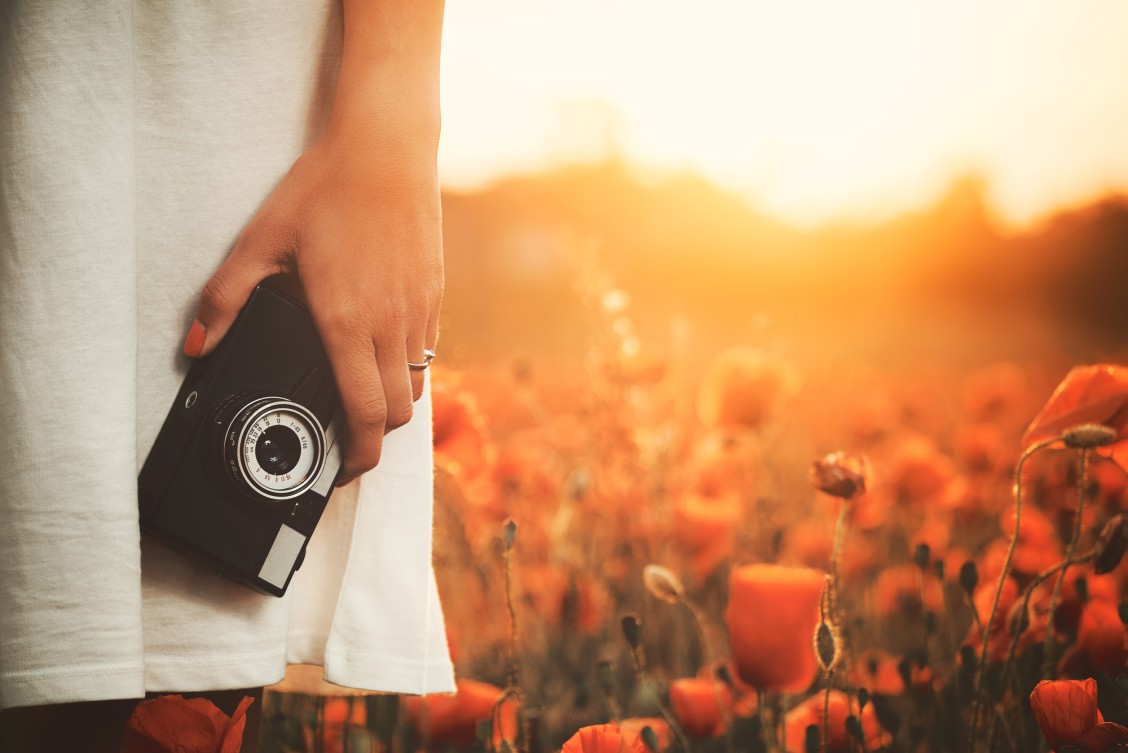 Close up of a woman in a white dress holding a vintage camera in a field of tulips to document her travel memories