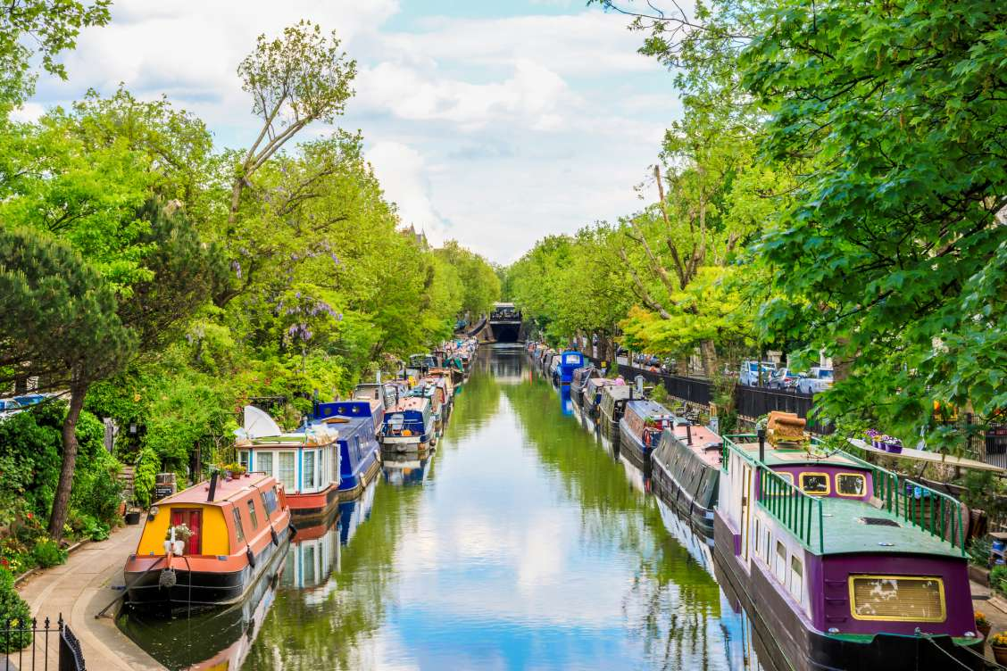Beautiful boats along Little Venice canal on a sunny day with green trees and blue skies