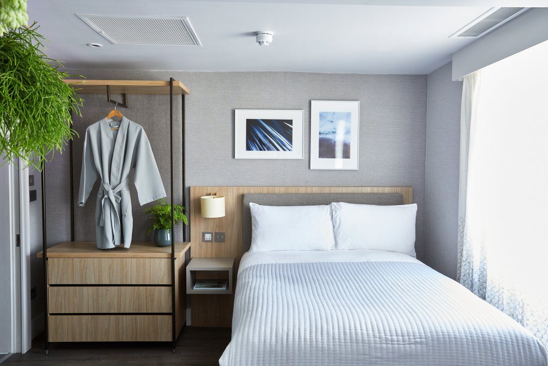 Beautifully crisp and clean room in Inhabit Hotel with fresh white linen and calming grey walls with wooden furniture