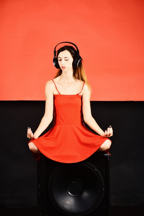Lady in red dress sitting in a yoga pose with headphones on
