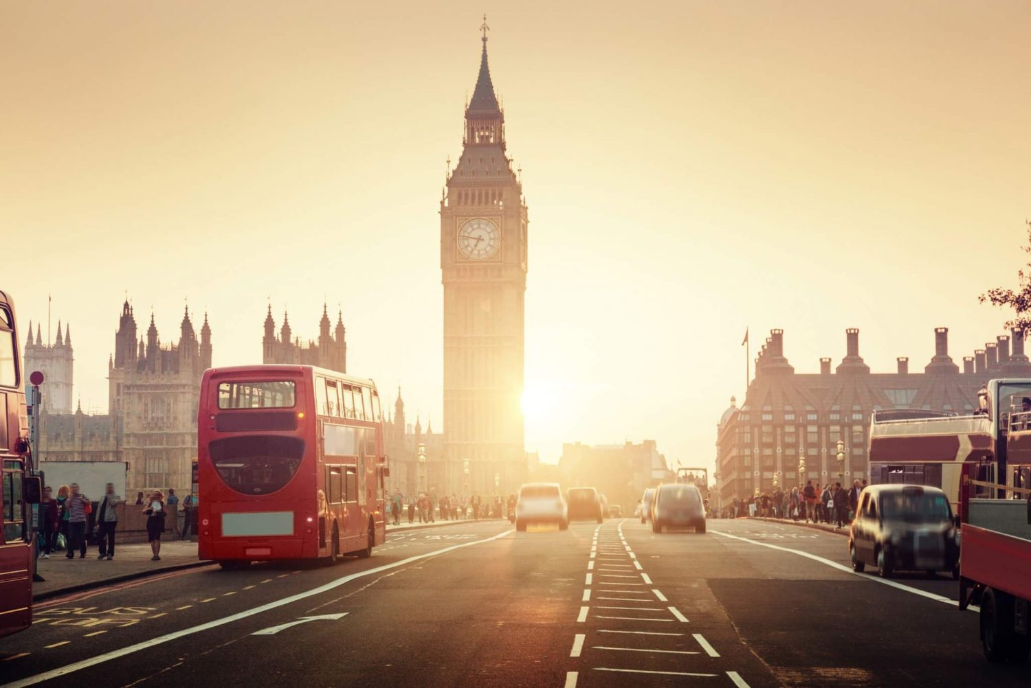 Westminster Bridge in London during sunset with Big Ben and a red bus shining bright