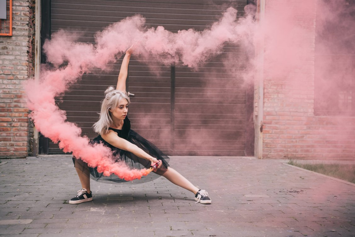 Woman in black dress and sneakers dancing on the street with pink smoke