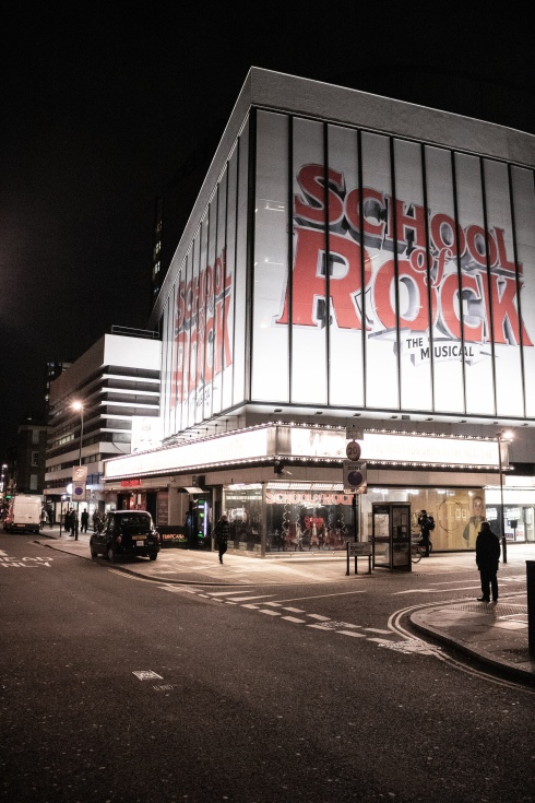 Outside the School of Rock show at night in London with the sign lit up brightly