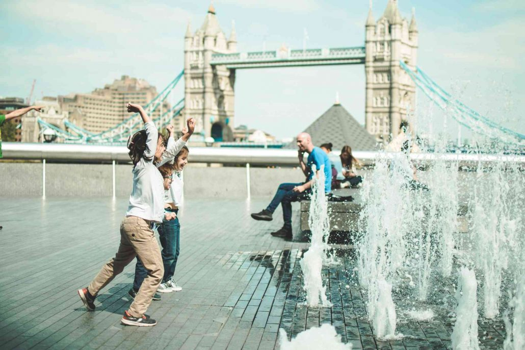 Kids playing in London with water fountains in front of Tower Bridge during a London visit with kids
